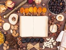 Autumn recipes. Turn an old book in an environment of nuts and fruits Royalty Free Stock Photography