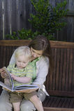 Turn the Page. A toddler turns the page of a book as he sits on his mother's lap on a wooden bench swing. Space on right and top for text Stock Photography
