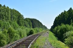 The turn of the railway rail goes into the perspective distance of the forest of grass and sky. Sunny clear warm summer day stock photos