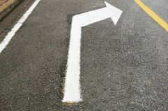Turn right sign. A photo of arrows on asphalt road showing a turn right sign stock image