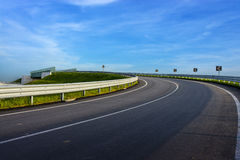 Turn in the road with guard rail. Guard rail on country road over a blue sky royalty free stock photos