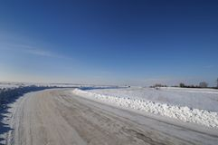 Turn in the road past the snow-covered fields Royalty Free Stock Photography