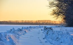Turn in the road past the snow-covered fields Royalty Free Stock Image