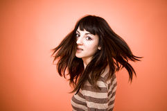 Turn In Surprise. Portrait of a teenage girl turning her head with a surprised expression. Hair is in motion around her head. Isolated on orange background stock image