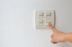 Turn switch off. One hand turning off lighting switch on whit wall background Royalty Free Stock Images