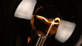 Turn on and turn off, close-up of retro vintage light bulb with tungsten technology built-in on black background, old style stock footage