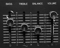 Turn up the volume. Bass, Treble, Balance, and Volume knobs on an aged black stereo system. Volume knob is raised to the top royalty free stock photography