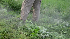 Turn view man with cutter tool mow weeds. Turn view man gardener with trimmer mow cut weeds in garden after rain. Water drops rise up stock footage