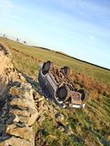 Turn for the worst. The morning after the night before. A four wheeled drive vehicle lies overturned after failing to take a bend and crashing through Stone wall royalty free stock photography