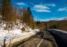 Turnaround on the mountain road in winter. Forested hills with snow on roadside under the clear blue sky Stock Photo