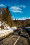 Turnaround on the mountain road in winter. Forested hills with snow on roadside under the clear blue sky Stock Photography