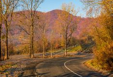 Turnaround on serpentine in mountains. Lovely autumnal morning with leafless trees Royalty Free Stock Images