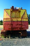 Turned back aged piece of machinery. Rear view of old rusted yellow and red machinery with bright blue sky on background royalty free stock photography