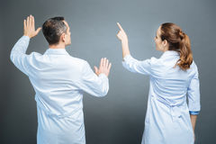 Turned back colleagues pretending to touch invisible screen. Innovative thinking. Waist up shot of medical workers standing next to each other and focusing their Royalty Free Stock Photo