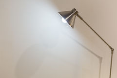 Turned on folding reading lamp against white wall Royalty Free Stock Images