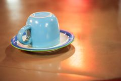 Turned over cup on a table in restaurant, isolate on colorful light backgrounds. Night light. Copy space royalty free stock photo