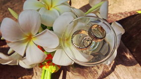 Turned over Wine Glass Wedding Rings on Top by White Flowers. Closeup turned over tall wine glass with wedding rings on top among beautiful white orchid flowers stock video