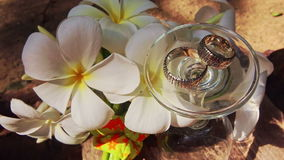 Turned over Wine Glass Wedding Rings on Top by White Flowers. Closeup turned over tall wine glass with wedding rings on top among beautiful white orchid flowers stock video footage