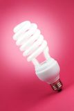 Turned on spiral bulb. Turned on fluorescent light spiral bulb on pink background Stock Photography