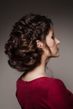 Turned to side gorgeous brunette girl with stylish haircut of curly hair turned back, posing with crossed arms. Brunette girl wear Royalty Free Stock Photo