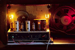 Turned on tubes of a vintage radio. Details of an old radio, view from  the back  in dark atmosphere Royalty Free Stock Photography