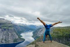 Turner, der auf seinen Händen auf dem Rand mit Fjord auf Hintergrund nahe Trolltunga steht norwegen lizenzfreies stockbild