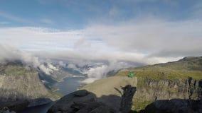 Turner, der auf seinen H?nden auf dem Rand mit Fjord auf Hintergrund nahe Trolltunga steht norwegen stock video