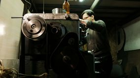 Turner está trabajando en un torno de torneado en la fábrica de las construcciones metálicas Industria de metal almacen de metraje de vídeo