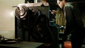 Turner está trabalhando em um torno de giro na fábrica das construções do metal Indústria de metal Medidas com um compasso de cal vídeos de arquivo