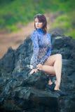 Turner girlgymnast Mädchen, das auf einem Stein sitzt Stockfotografie