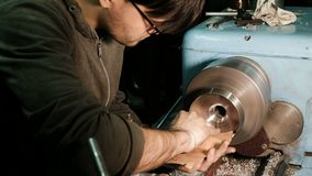 Turner grinds the metal part fixed on the lathe with sandpaper stock video