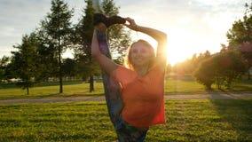 Turner hebt ein Bein in einer vertikalen Schnur in einem Stadtpark auf Sonnenuntergang, Kamerabewegung an lizenzfreie stockfotos