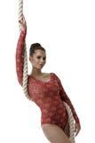 Turner im schönen roten Trikotanzug, der mit Seil aufwirft Stockbild