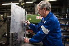 Turner młynarka robi pomiarom szkotowy metal używać strugarkę zdjęcie stock