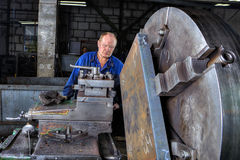 Turner machine operator controls processing of metal big turning Royalty Free Stock Photos