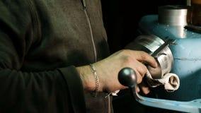 Turner mide las dimensiones del objeto del metal con un calibrador Trabajo sobre un torno metrajes