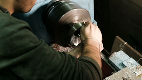 Turner muele la pieza de metal fijada en el torno con papel de lija almacen de metraje de vídeo