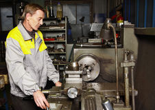 Turner processes metal workpiece on turning lathe. Stock Photos