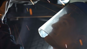 Turner sawing under the car. Turner sawing bottom under the car stock video footage