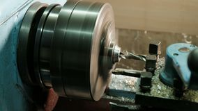 Turner is working on a turning lathe at the metal constructions factory. Heavy industry and metalwork. Accuracy metal. Cutting and detail drilling stock footage