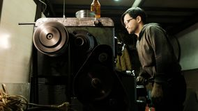 Turner is working on a turning lathe at the metal constructions factory. Metal industry stock images