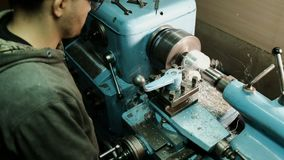 Turner is working on a turning lathe at the metal constructions factory. Metal industry stock footage