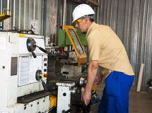 The mechanic works at the lathe at factory. The turner works at the lathe on production Stock Photo