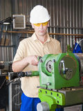 The mechanic works at the lathe at factory. The turner works at the lathe on production Stock Photography