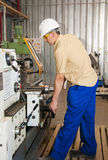 The mechanic works at the lathe at factory. The turner works at the lathe on production Stock Photos