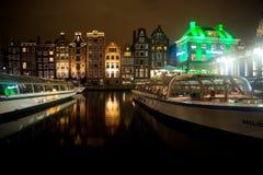 Turnera fartyg på flodkanalen och historiska byggnader i Amsterdam Arkivbild