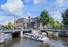 Turnera fartyget med turister på en kanal, Amsterdam, Nederländerna Royaltyfri Foto