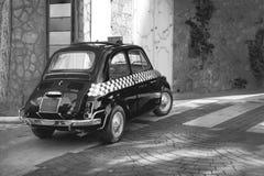 Turnerar den roliga bilen för den lilla svarta klassiska italienska Retro taxien, lopp, och turism, svartvita Italien arkivfoton