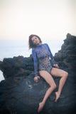 Turnermädchen, das auf einem Stein sitzt Stockfotos