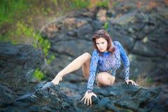 Turnermädchen, das auf einem Stein sitzt Stockfoto